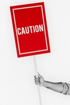 Vorsichtswarnungskarte in der hand halten