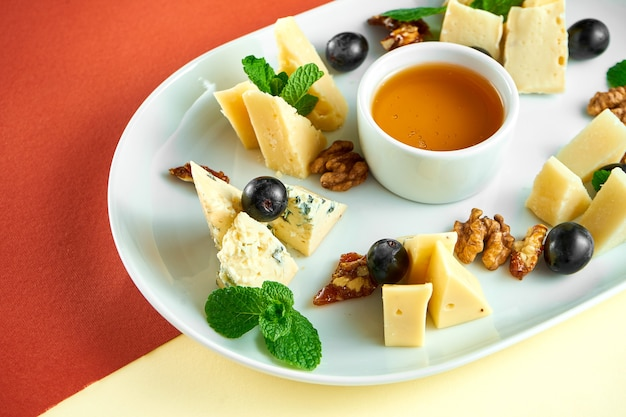 Vorspeise - antipasti-käseplatte mit dorblu, parmesan und camembert, honig, nüssen auf heller oberfläche