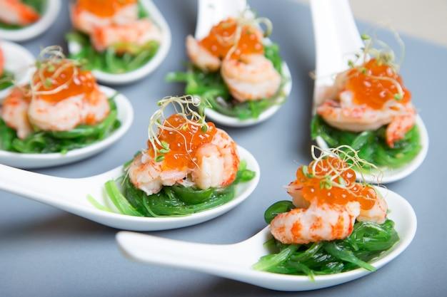 Vorspeise aus algen-chuka, krabben und kaviar auf portionierten spoos. selektiver fokus, nahaufnahme.