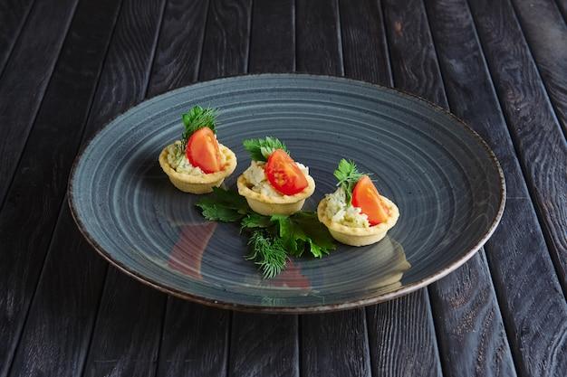 Vorspeise für den empfang. törtchen mit kartoffelpüree, frischkäse und eingelegter gurke