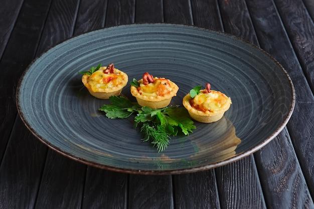 Vorspeise für den empfang. törtchen mit speck, geschmolzenem käse und pilz