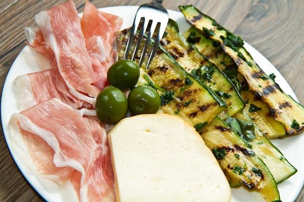 Vorspeise mit rohem schinken, käse und gegrilltem gemüse