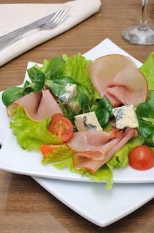 Vorspeise mit schinken und blauschimmelkäse in salatblättern mit feldsalat