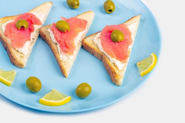 Vorspeise, offenes sandwich mit lachs auf einem blauen teller auf weißem hintergrund. traditionelle italienische oder skandinavische küche. konzept der richtigen ernährung und gesunden ernährung