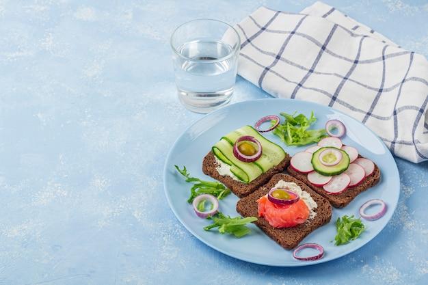 Vorspeise, offenes sandwich mit verschiedenen belägen auf einem teller und einem glas wasser auf blauem hintergrund. traditioneller italienischer oder skandinavischer snack