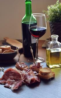 Vorspeise von schinken serrano mit geröstetem brot und einem glas wein