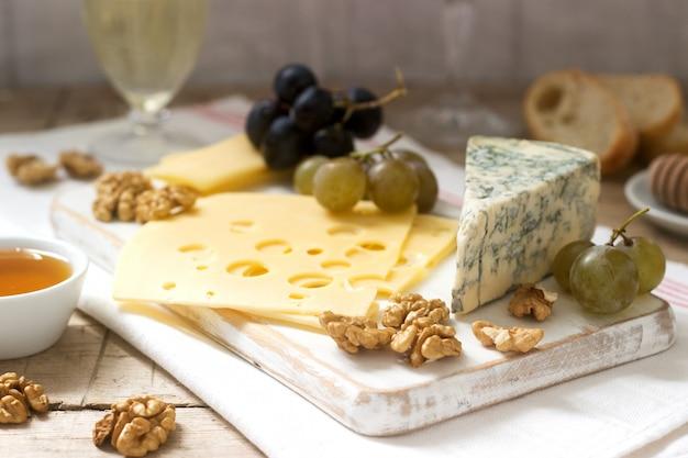 Vorspeisen aus verschiedenen käsesorten, trauben, nüssen und honig, serviert mit weiß- und rotwein