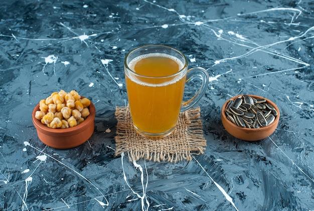 Vorspeisen in schalen neben einem glas bier auf textur, auf dem blauen tisch.