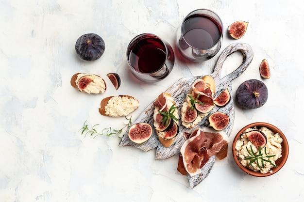 Vorspeisen. sandwich mit prosciutto, frischkäse und feigen. antipasti mit rotwein. banner, menürezept. ansicht von oben