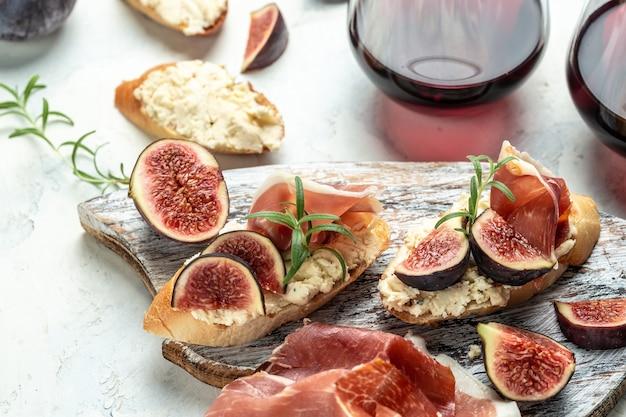 Vorspeisen, sandwich mit schinken, frischkäse und feigen. antipasti-snacks und rotwein in gläsern. authentisches traditionelles spanisches tapas-set. ansicht von oben.