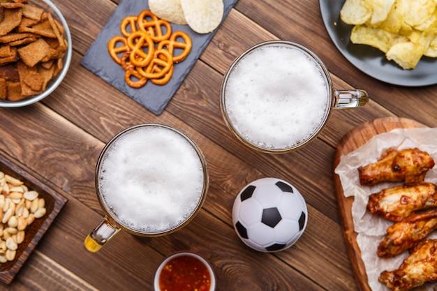 Vorspeisen und bier auf dem tisch für die fußballparty und schauen sie sich das fußballspiel an.