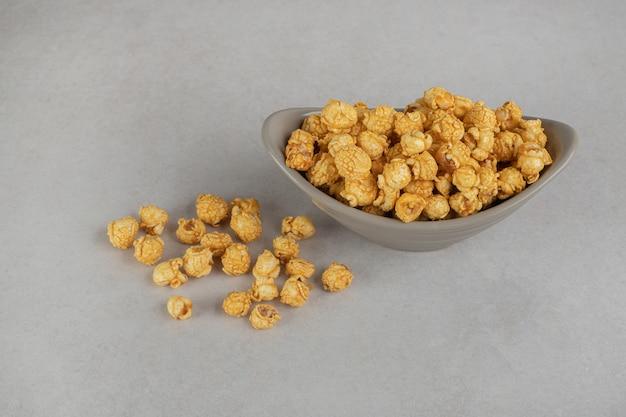 Vorspeisenschale gefüllt mit einer portion karamellbeschichtetem popcorn auf marmor.