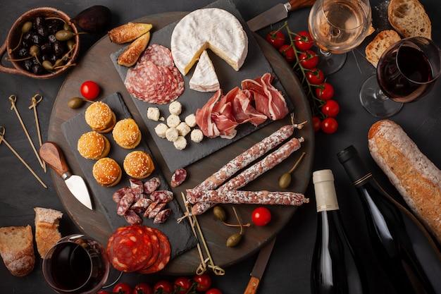 Vorspeisentabelle mit verschiedenen antipasti, käse, wurstwaren, imbissen und wein.