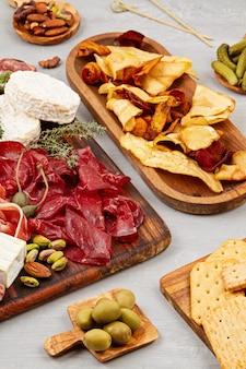 Vorspeisentisch mit verschiedenen antipasti, wurstwaren, snacks und wein. wurst, schinken, tapas, oliven, käse und cracker für buffetpartys. draufsicht, flach liegen