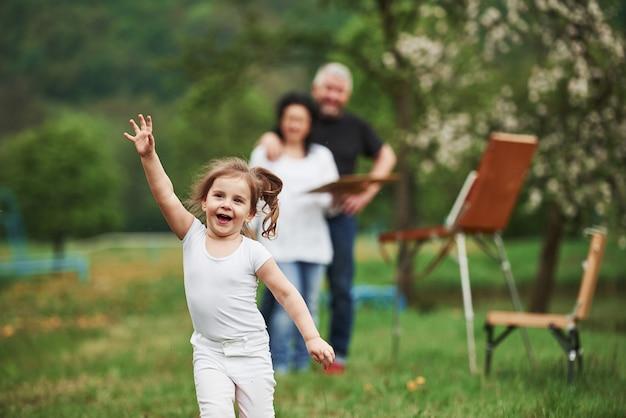 Vorwärts rennen. großmutter und großvater haben spaß im freien mit enkelin. malkonzeption