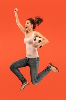Vorwärts zum sieg. die junge frau als fußballspielerin springt und tritt den ball an