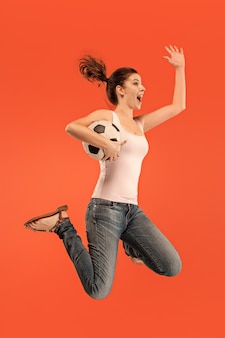 Vorwärts zum sieg. junge frau als fußballspielerin springt und tritt ball auf rot