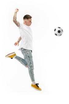 Vorwärts zum sieg. junger mann als fußballfußballspieler, der den ball im studio auf einem weißen hintergrund springt und tritt. fußballfan und weltmeisterschaftskonzept.