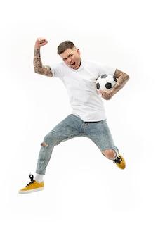 Vorwärts zum sieg. junger mann als fußballfußballspieler, der den ball im studio auf einem weißen hintergrund springt und tritt.