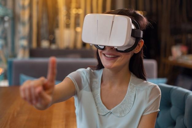 Vr-möglichkeiten. optimistische schwule aufrichtige frau, die hand erhebt, während sie grinst und vr-headset trägt