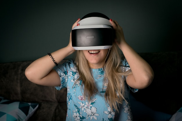 Vr virtuelle realität. mädchen möchte erfahrung mit brillen eines vr-headsets sammeln. erstaunliche emotionen, kühle ruhe, neustart. virtual-reality-brillen liegen in neonlichtern. konzept der visuellen realität