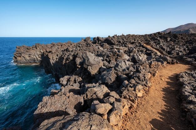 Vulkanische küstenlandschaft. felsen und lavabildungen in kanarischen inseln, spanien. hochwertiges foto