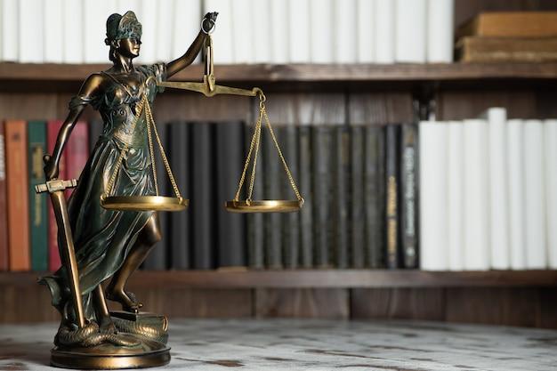 Waage der gerechtigkeit, lady justice, gesetzesbibliothekskonzept, gesetzesbücher im hintergrund.