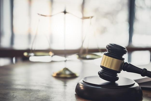 Waage der gerechtigkeit und des hammers auf klingendem block, gegenstand und gesetzbuch zur arbeit mit richterzustimmung