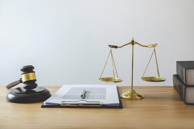 Waage der gerechtigkeit und gavel über klangblock, objekt und gesetzbuch zur arbeit mit dem richter