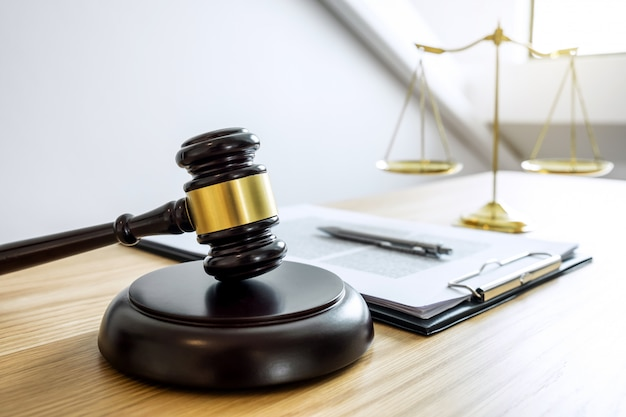 Waage der gerechtigkeit und gavel über klangblock, objekt und gesetzbuch zur arbeit mit richter