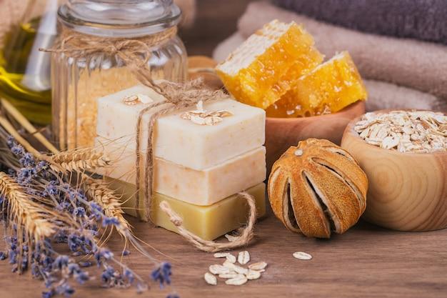 Waben, kosmetisches öl, meersalz, hafer und handgemachte seife mit honig auf rustikalem holzhintergrund. natürliche zutaten für selbstgemachte gesichts- und körpermasken oder peelings. gesunde hautpflege. spa-konzept.