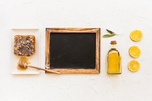 Waben-, olivenöl- und zitronenscheiben mit schöpflöffel und leerem schiefer