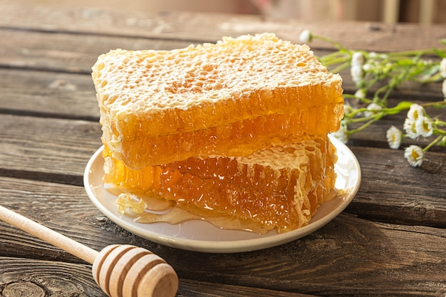 Wabenstücke auf einem teller und einem honiglöffel