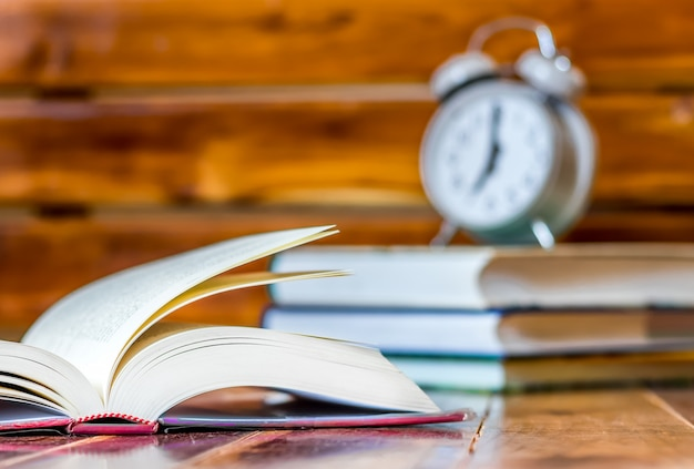 Wachen sie alarm auf und lesen sie buch auf hölzerner tabelle mit sonnenaufgang