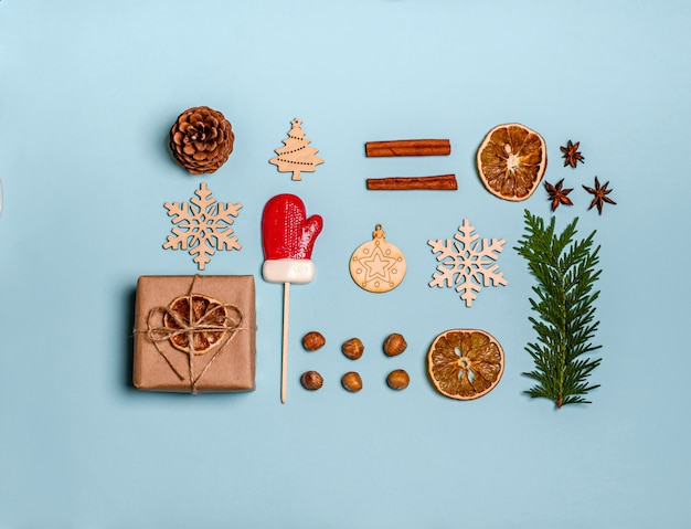 Wacholderzweig, zimt, anis, geschenkbox, trockene orangen, holzspielzeug, weihnachtsbonbonkaramellen, tannenzapfen und nüsse