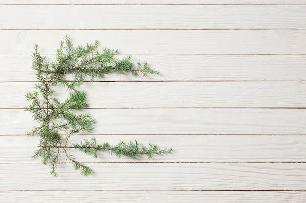 Wacholderzweige auf einem weißen hölzernen hintergrund. weihnachten und neu