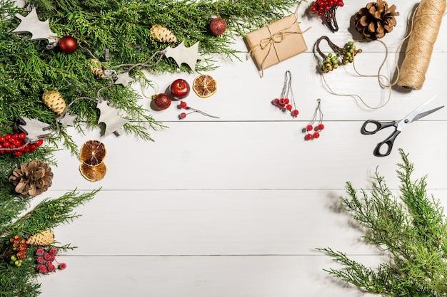 Wacholderzweige mit weihnachtsdekor. weihnachten, neujahr hintergrund. koniferenzweige des wacholders. ansicht von oben, flaches design. weihnachtsbaum auf weißem hintergrund aus holz.