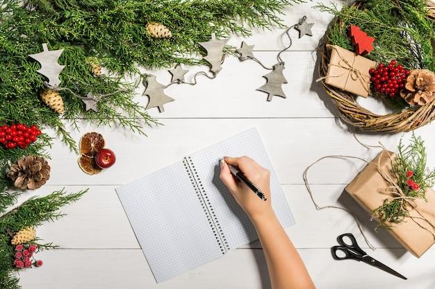 Wacholderzweige mit weihnachtsdekor. weihnachten, neujahr hintergrund. koniferenzweige von wacholder, notizbuch und einem stift. ansicht von oben, flaches design. weihnachtsbaum auf weißem hintergrund aus holz.