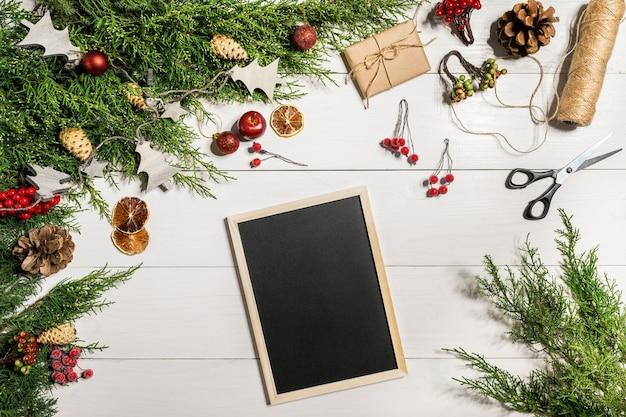 Wacholderzweige mit weihnachtsdekor. weihnachten, neujahr hintergrund. koniferenzweige von wacholder und schwarzer schreibtafel. ansicht von oben, flaches design. weihnachtsbaum auf weißem hintergrund aus holz.