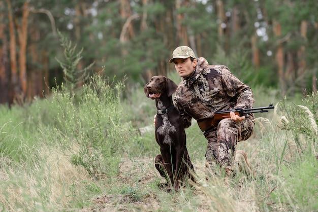 Wachsamer jäger und hund bei der waldtierjagd.
