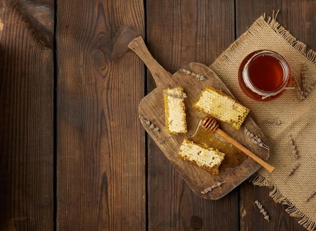 Wachsbienenwabe mit honig auf holzbrett und holzlöffel, brauner tisch, kopierraum