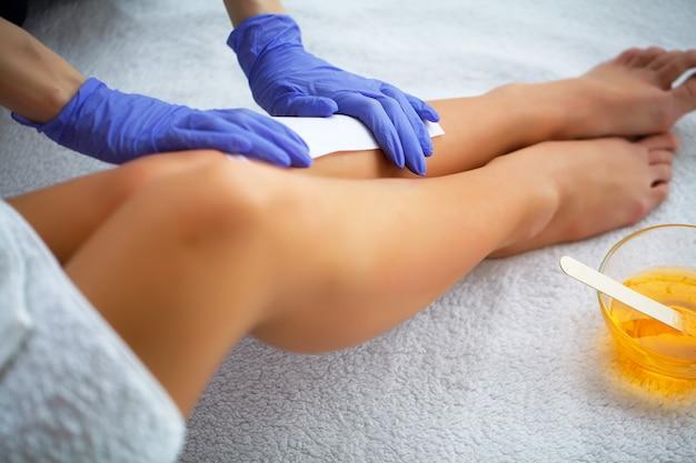 Wachsen. kosmetiker, der das bein der frau im badekurortsalon einwächst