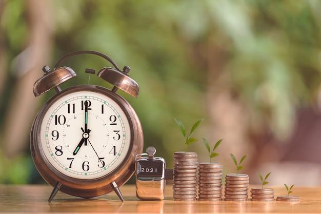 Wachsende grafik des geldmünzenstapels mit wecker, um konzeptinvestitionsgeschäft und finanzen zu profitieren