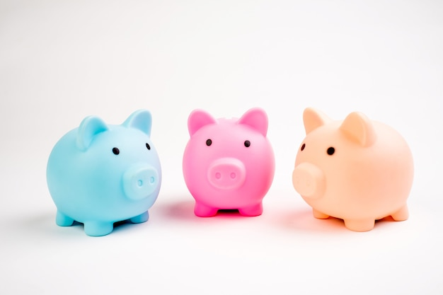 Wachsende investition - drei sparschweine unterschiedlicher farbe isoliert auf weiß