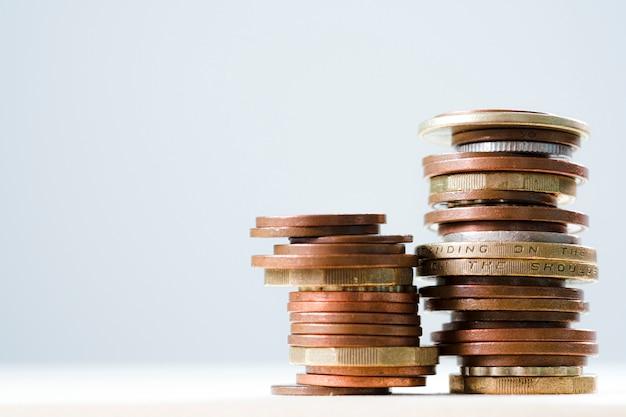 Wachsende münzen der nahaufnahme, die mit weißem hintergrund stapeln.