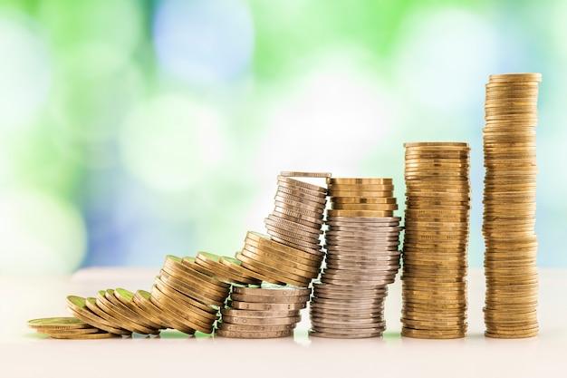 Wachsende münzenstapel mit grünem und blauem funkelndem bokeh.