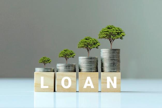 Wachsende pflanze auf münzstapel und holzblock mit darlehenstext, finanzierungsideen und kreditwachstum.
