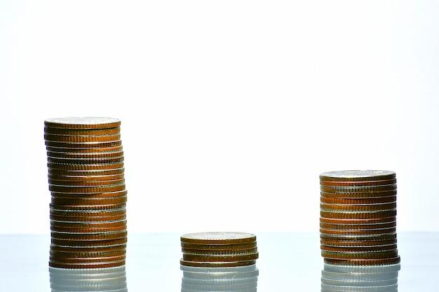Wachsendes geschäft des geldmünzenstapels auf lokalisiertem weißem hintergrund, ausgabengeldkonzept.