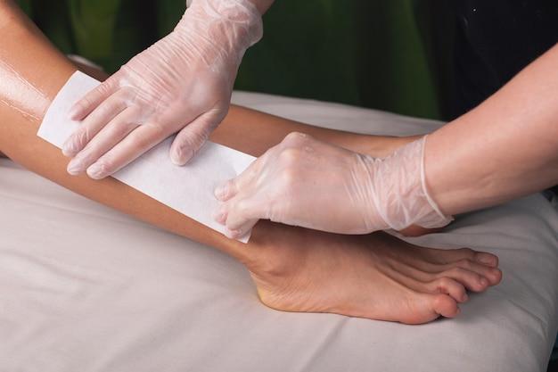 Wachsverfahren an beinen, die in einem spa-salon von einem kaukasischen therapeuten mit handschuhen durchgeführt wurden