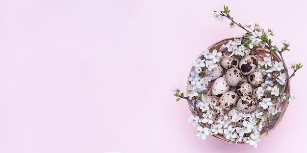 Wachtel-ostereier in einem korb mit blumen auf einem rosa hintergrund.
